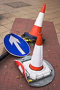 Traffic arrow bent and laying on pavement after road traffic accident, now guarding hazard to passing pedestrians.