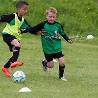 U8 player Conor Byrne pushes off a defender during the Avenue Utd Summer Soccer Camp