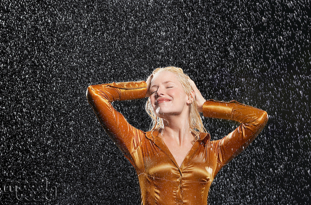 Woman Standing in Rain arms raised letting raindrops fall on face