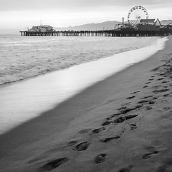 Santa Monica Pier sunset black and white vertical photo with footprints in the sand along the Pacific Ocean. Santa Monica is a coastal beach city in Southern California in the United States. Copyright ⓒ 2017 Paul Velgos with All Rights Reserved.