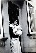 woman with newborn baby in the door opening England 1940s