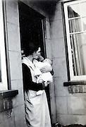 woman with newborn baby in the door opening England 1940s