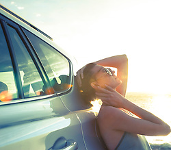 Woman Leaning against Car at Sunset