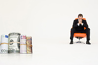 Money rolls with pensive businessman on chair representing financial problems