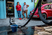Women watch as water leaks from a tanker pipe in the streets of Icatapec. Studies suggest that up to 40% of Mexico City's water is lost to leaky infrastructure.