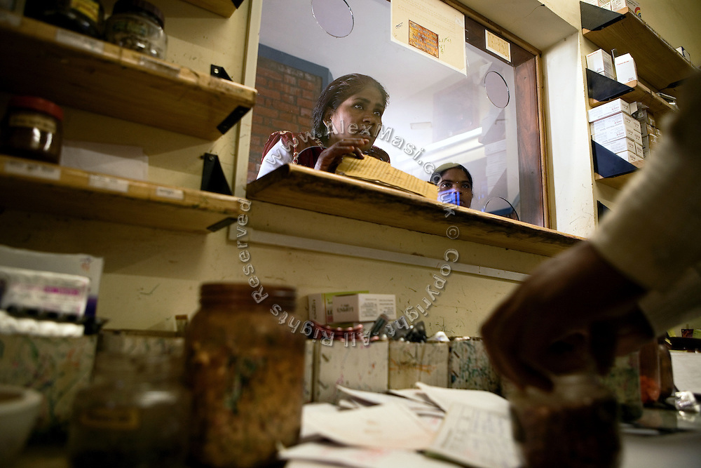 A patient is waiting for a medicinal Ayurvedic mix to be prepared by a physician at the Sambhavna Clinic in Bhopal, Madhya Pradesh. Sambhavna offers free medical services to the survivors of the 1984 Bhopal Industrial Disaster and has more than 30.000 registered patients.
