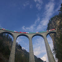 The Glacier Express train crosses high above the Landwasser river into a tunnel on the iconic Landwasser viaduct in Fillisur as part of the Rhaetian Railway line