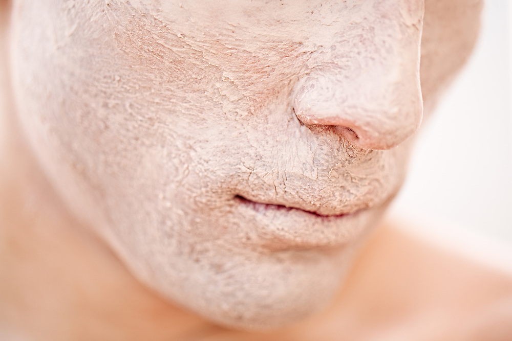 A close-up of a young male model's face with foundation applied to it.