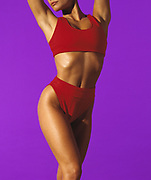 Young woman wearing red exercise attire doing aerobics in front of purple background