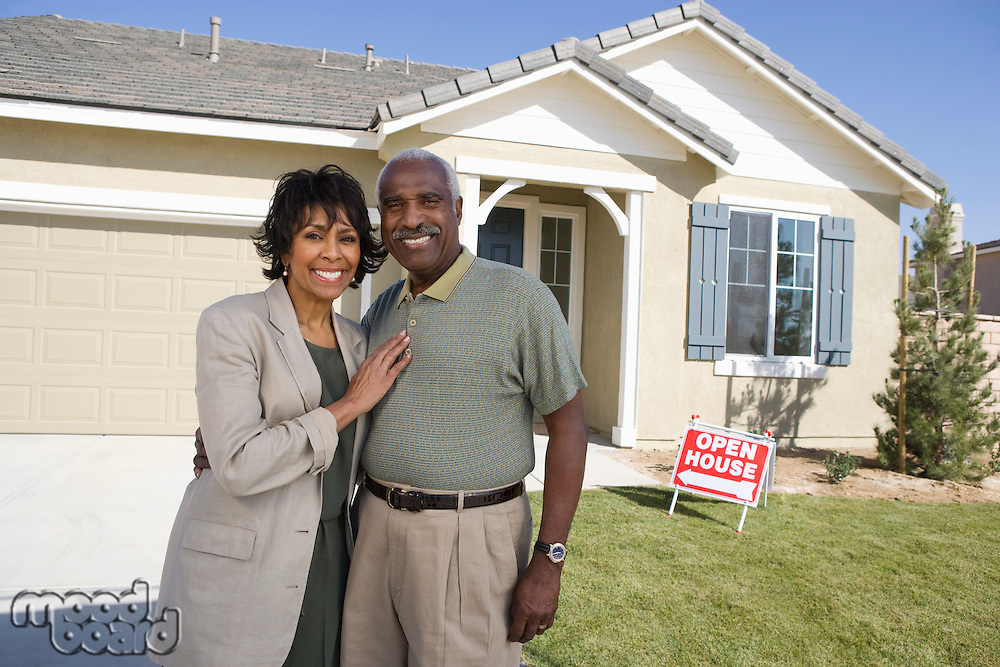 Mid-adult couple in front of new house, portrait