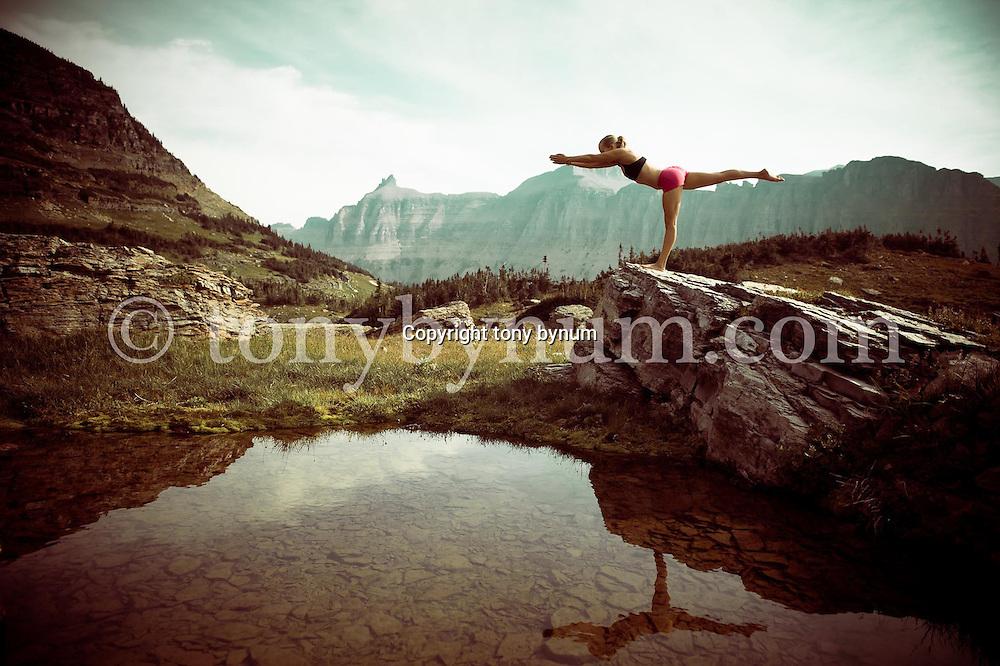 woman yoga balance on rock above lake in dramatic mountians