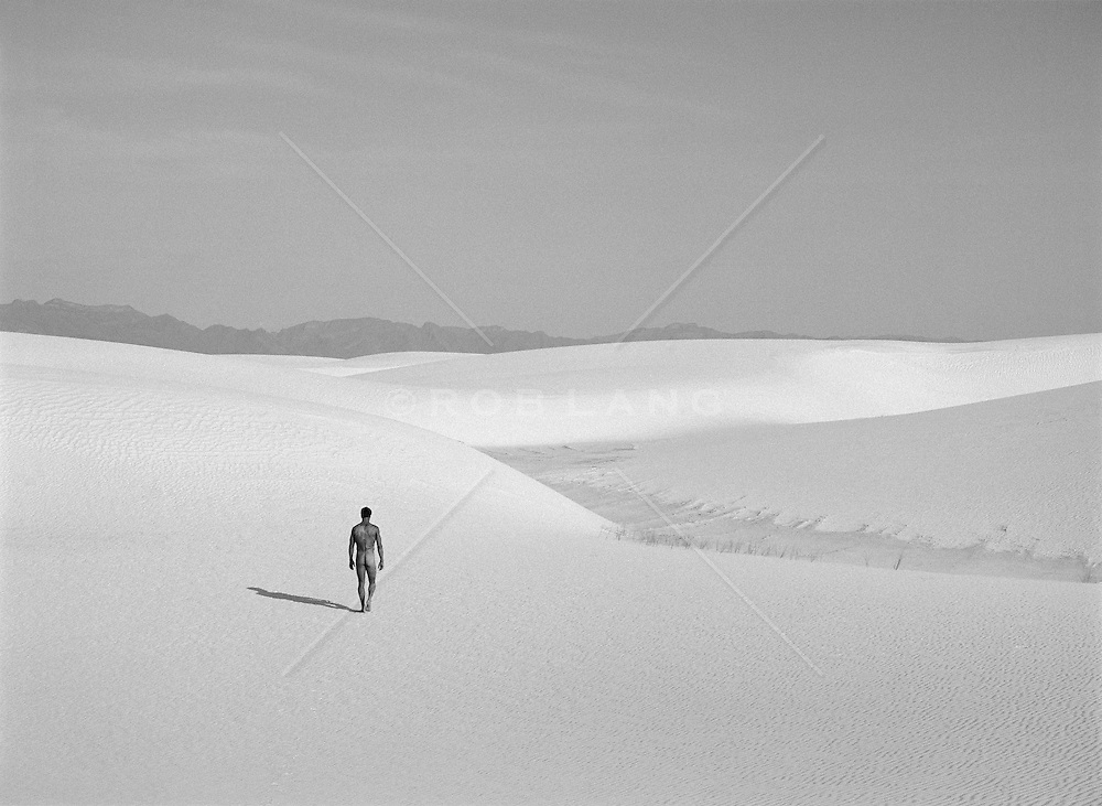 Naked man walking on a sand dune in White Sands, NM