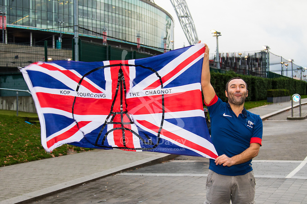 Wembley Stadium, London, November 17th 2015. Hours befor kick-off French and England fans begin to gather outside Wembley Stadium as both England and France national teams are poised to play in an emotional tie just days after the tragic death of 130 people in the Paris Islamist attacks. PICTURED:  A French football fan with his Eiffel Tower symbol on his flag.  // Licencing Contact: paul@pauldaveycreative.co.uk Mobile 07966 016 296