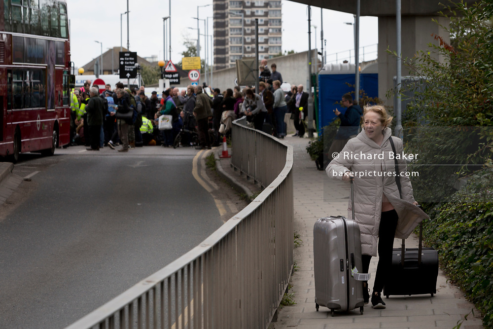 As environmental activists protest about Climate Change during the occupation of City Airport (London's Business Travel hub) in east London, a recently-arrived passenger tries to find transport away from the blockade on the fourth day of a two-week prolonged worldwide protest by members of Extinction Rebellion, on 10th October 2019, in London, England.