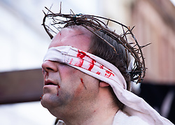 © Licensed to London News Pictures. 19/04/2019. Walsall, West Midlands, UK. Walking the way of the Cross. For over twenty years the Walsall Town Centre Ministry re-enact the scene of Jesus carrying the cross through the Town Centre. Hundreds of people gather at the bottom of the Town Centre as an actor playing the role of Jesus is guarded by soldiers. The procession then makes it's way through the busy shopping centre stopping at various points to recite prayers or sing hymns. The parade finishes in the central square where the Cross being carried is erected and a service takes place for all denominations.  Photo credit: Dave Warren/LNP