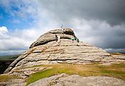 People scrambling on a granite tor near Haytor, Dartmoor national park, Devon, England