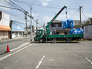 Sacks filled with radiation-contaminated debris are lifted onto a truck in the center of Tomioka, Japan. Over 5.5 million bags of radioactive debris have now been accumulated, however a 10-ton truck can only carry seven bags at a time leaving a huge question mark over how to get the millions of bags to landfill.