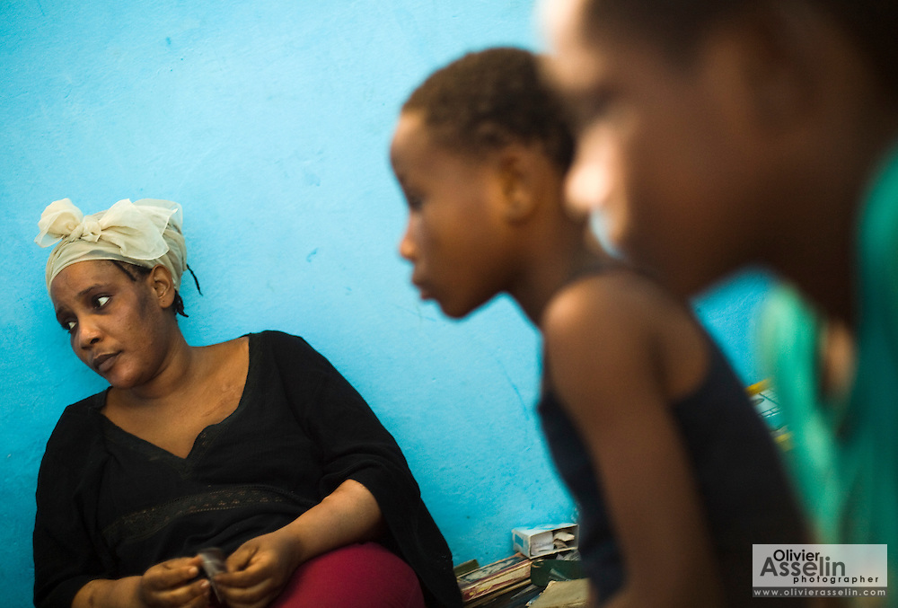 Liberian national Nina Jallah sits with her two children in the room where they live in Dakar, Senegal on Thursday July 16, 2009. Nina says she's not following the Charles Taylor trial and wishes people could just move on.