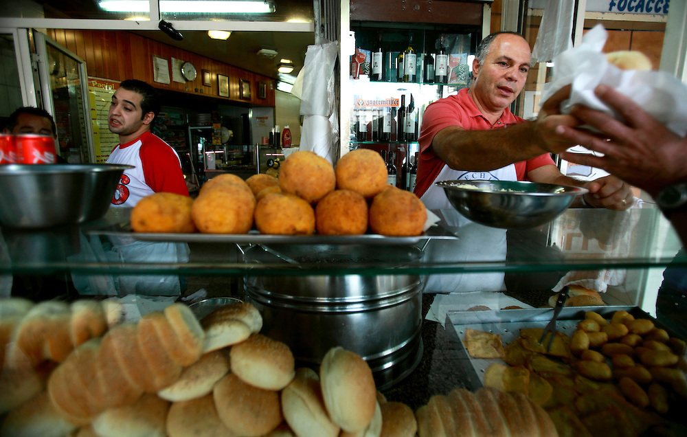 Sicilian selling fried rice balls, Palermo, Sicily. Road side shops at every street corner sell fried or cooked food.
