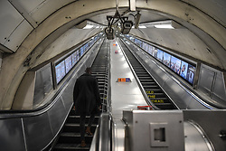 © Licensed to London News Pictures. 20/03/2020. London, UK. Oxford Circus at 8pm, a man takes the escalator to street level on what would usually be one of the busiest nights of the week. London's underground network that at its peak handles 5 million passenger journeys a day was left all but abandoned on Friday as the coronavirus outbreak escalated. This latest phase of social distancing follows as the government announced the immediate closure of bars, pubs and restaurants to reduce person to person contact and virus transmission. Photo credit: Guilhem Baker/LNP