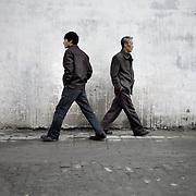 A Uighur man and a Chinese man crossing the streets of Urumqi, Xinjiang, China