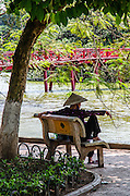 Woman sitting by Hoan Kiem Lake Hanoi