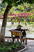 Woman sitting by Hoan Kiem Lake Hanoi