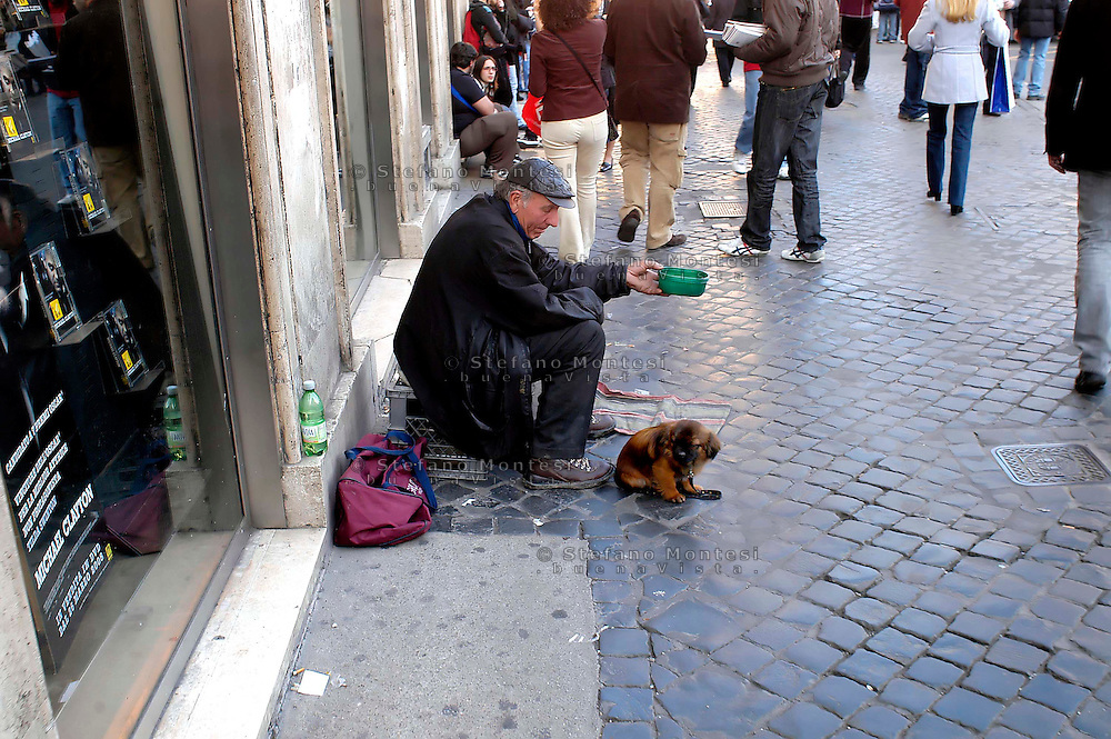 Roma  Aprile 2008.Un uomo con il cane chiede L'elemosina Largo Argentina. A man whit the dog  begging in largo Argentina..