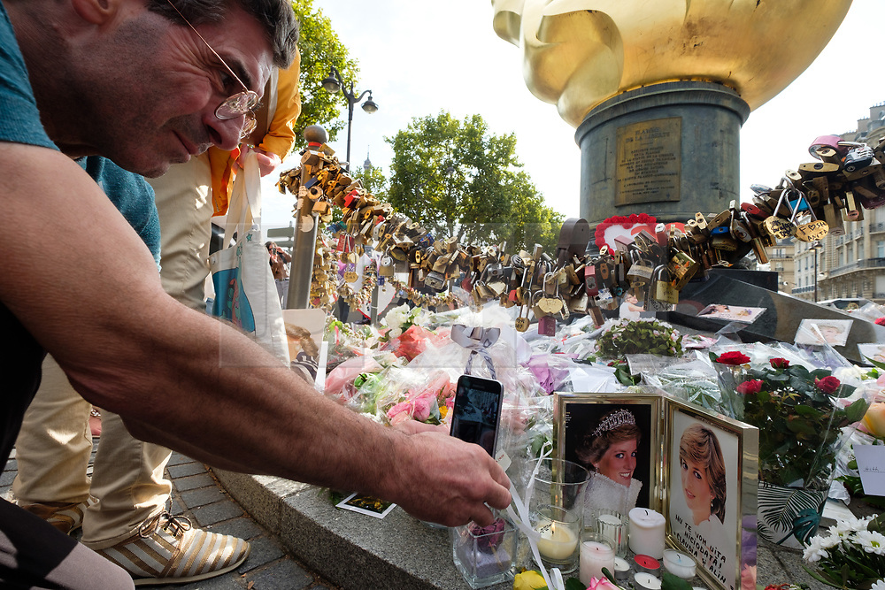 © Licensed to London News Pictures. 31/08/2017. Paris, France. A man take a mobile phone photo of the tributes to the late Princess Diana above the Post de l'Alma tunnel in Paris.  Princess Diana died with Dodi Al-Fayed in a car crash on 31st August 1997. Photo credit: Ray Tang/LNP