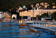 View of Opatija in early morning light, with concrete ocean-front and steps into water in foreground. Opatija, Croatia