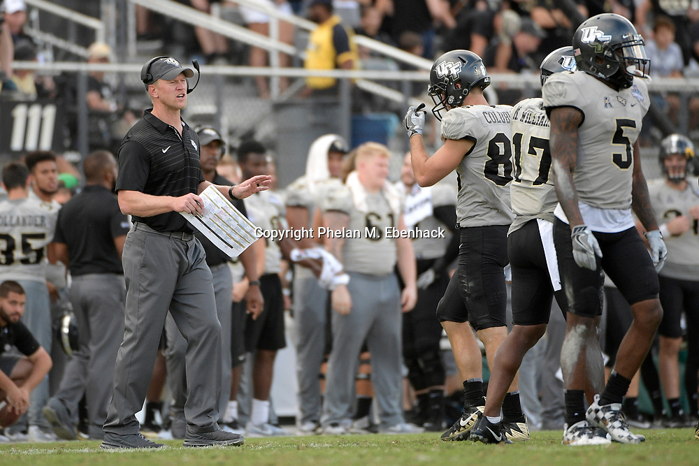 Central Florida head coach Scott Frost, left, instructs the team from the sideline during the second half of the American Athletic Conference championship NCAA college football game against Memphis Saturday, Dec. 2, 2017, in Orlando, Fla. Central Florida won 62-55. (Photo by Phelan M. Ebenhack)