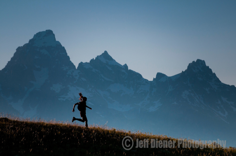 A trail runner traverses a ridgeline in front of the Tetons in Jackson Hole, Wyoming.