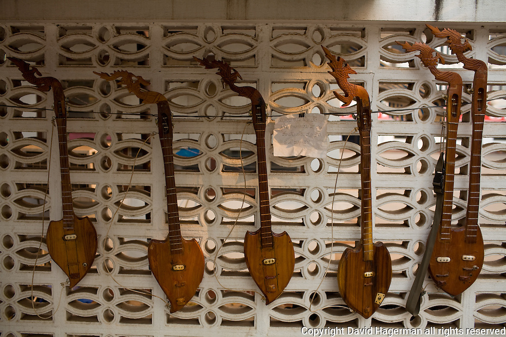 Seung, a stringed musical instrument hang at the ready on a Vientiane street.