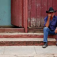 Central America, Cuba, Remedios. Cuban man in hat sitting on steps in Remedios.