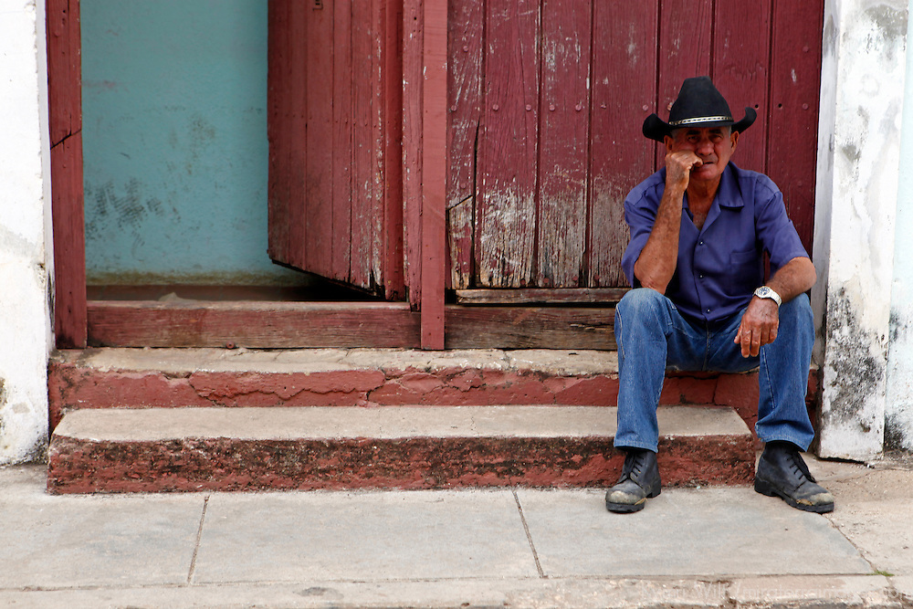 Central America, Cuba, Remedios. Cuban man in hat sitting on steps in Remedios.