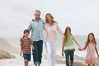 Family with three children (5-6 7-9 10-12) walking on beach
