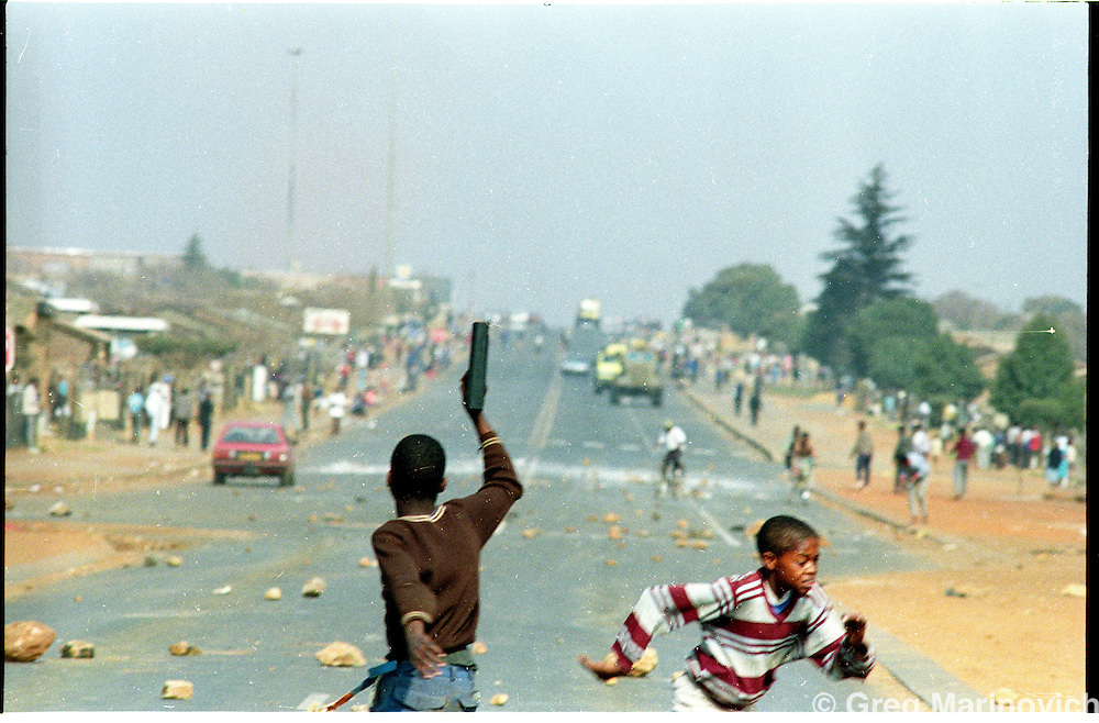 Sebokeng, 12/8/1991, South Africa..Kid brandishes a toy gun at police armoured vehicles as his friend spots another police behicle coming up a side street. Greg Marinovich. 2 of 3.