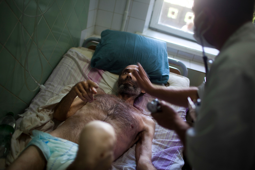 A doctor checks on a patient in the intensive care unit at the TB hospital in Balti.