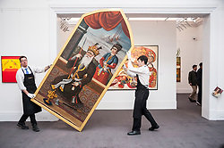 "© Licensed to London News Pictures. 02/10/2015. London, UK. Sotheby's technicians carry a ""Monumental Historical Qajar portrait of King Jamshid"" (est. £250k - 350k) at the preview of Indian and Islamic Art Week at Sotheby's which runs from 2 to 7 October.  Photo credit : Stephen Chung/LNP"