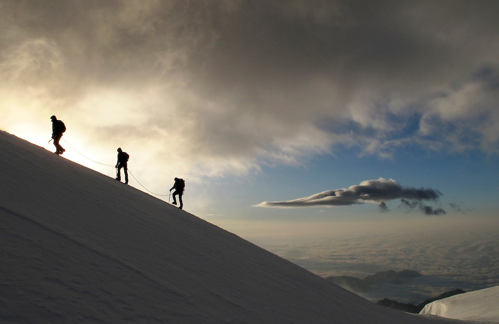 Alpinists at dawn, nearing the summit of Zumsteinspitze, 4563m, Swtizerland / Italy border, 13th July 2009.