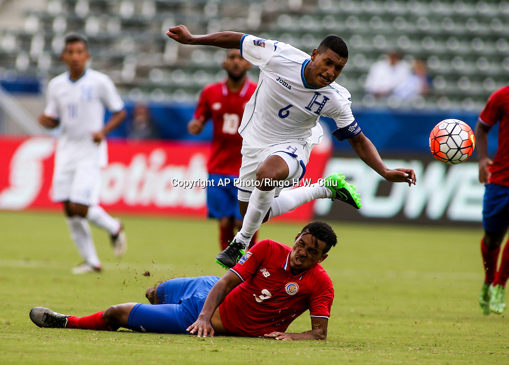 Honduras midfielder Bryan Josue Acosta Ramos #6 jumps over Costa Rica defender Julio Cascante #3 in the first half of a CONCACAF men's Olympic qualifying soccer match in Carson, Calif., Sunday, Oct. 4, 2015. (AP Photo/Ringo H.W. Chiu)