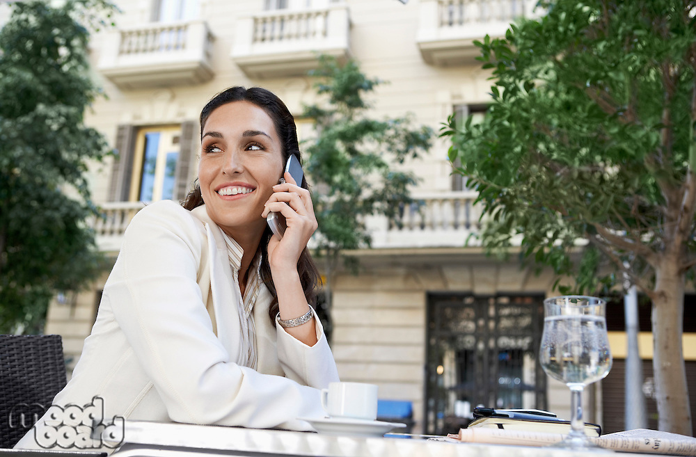 Businesswoman using mobile phone at outdoor cafe