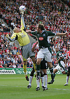 Photo: Lee Earle.<br /> Southampton v Plymouth Argyle. Coca Cola Championship. 24/09/2005. Southampton keeper Antti Niemi punches clear a Plymouth corner as Micky Evans tries to head the ball.