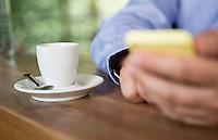 Österreich, Geschäftsmann mit Smartphone bei Kaffeepause an Theke in Restaurant, Casual Look, Nahaufnahme