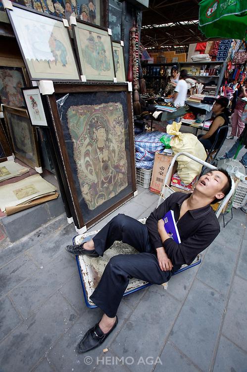 Panjiayuan weekend market. Shop owner having a nap.