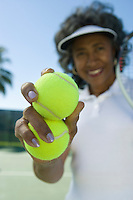 Woman holding tennis balls, portrait