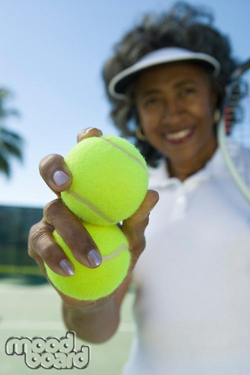 Woman holding tennis balls, portrait