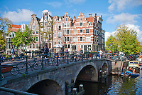 Amsterdam, Holland. Bridge over a canal with bicycles parked along it's edge.  Traditional Dutch buildings rise in the background.