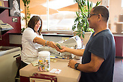 Owner Roula Perivoliotis gives a customer change at Mil's Diner in Milpitas, California, on September 12, 2014. (Stan Olszewski/SOSKIphoto)