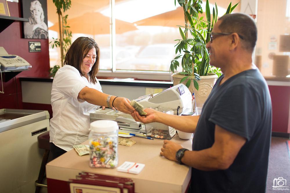 Owner Roula Perivoliotis gives a customer change at Mil's Diner in Milpitas, California, on September 12, 2014. (Stan Olszewski/SOSKIphoto)